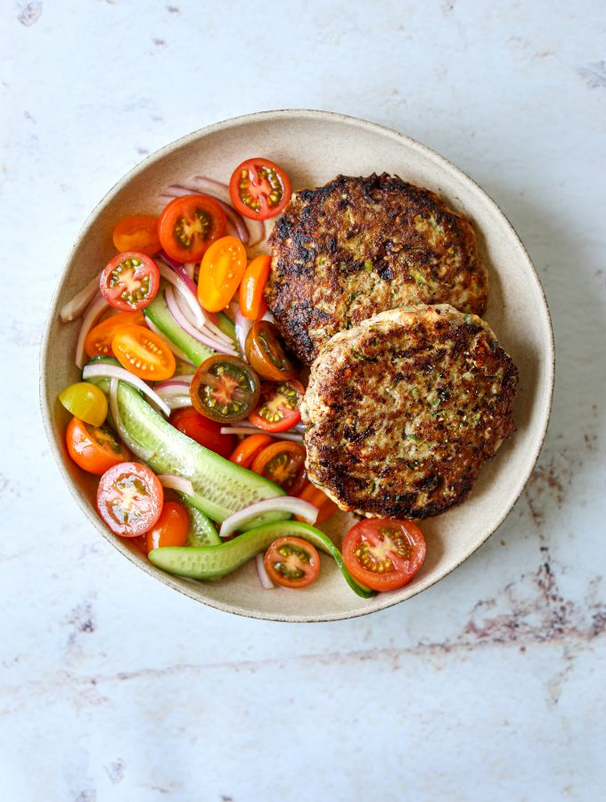 Two turkey and zucchini burgers on a plate with a side of tomato and cucumber salad