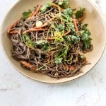 A ceramic bowl filled with Miso-Tahini Soba Noodles topped with sliced scallion and cilantro