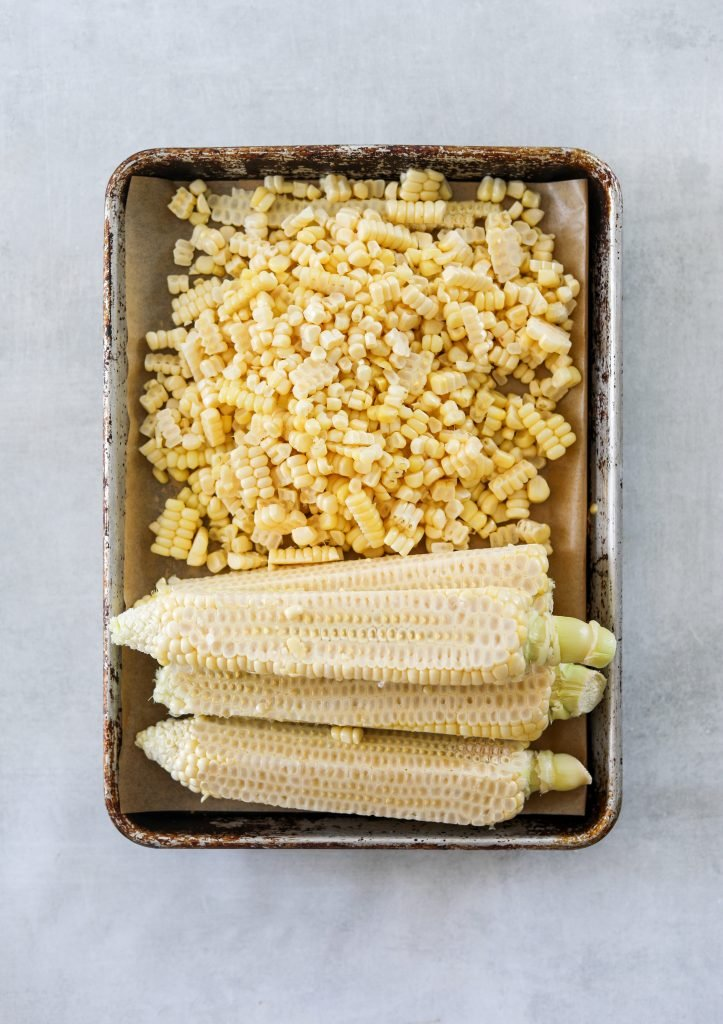corn kerners and corn cobs on a baking tray