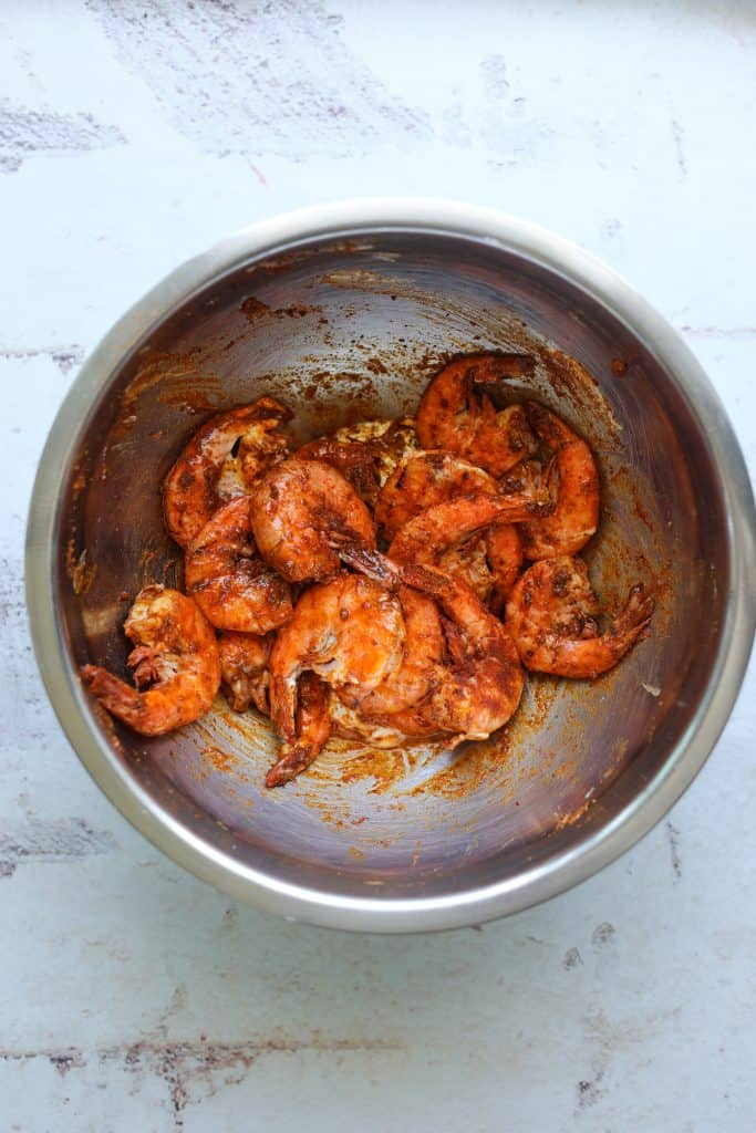 a mixing bowl with grilled shrimp tossed with old bay seasoning, butter and lemon