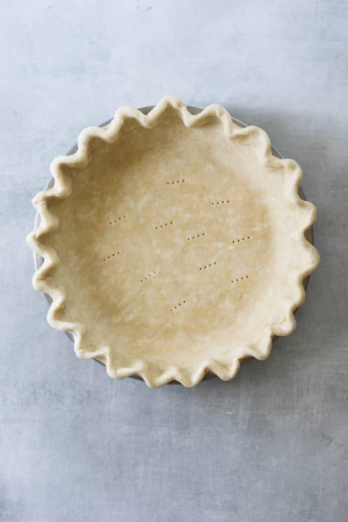 a raw pie crust in a pie tin