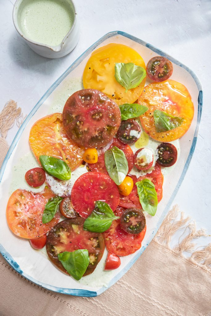 a platter filled with heirloom tomato salad with buttermilk-basil dressing
