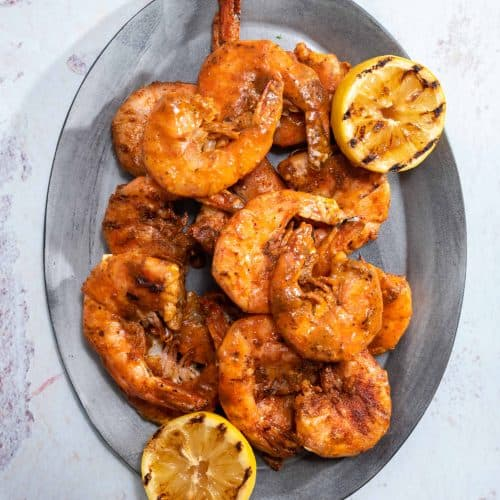 an oval platter filled with grilled shrimp and grilled lemons