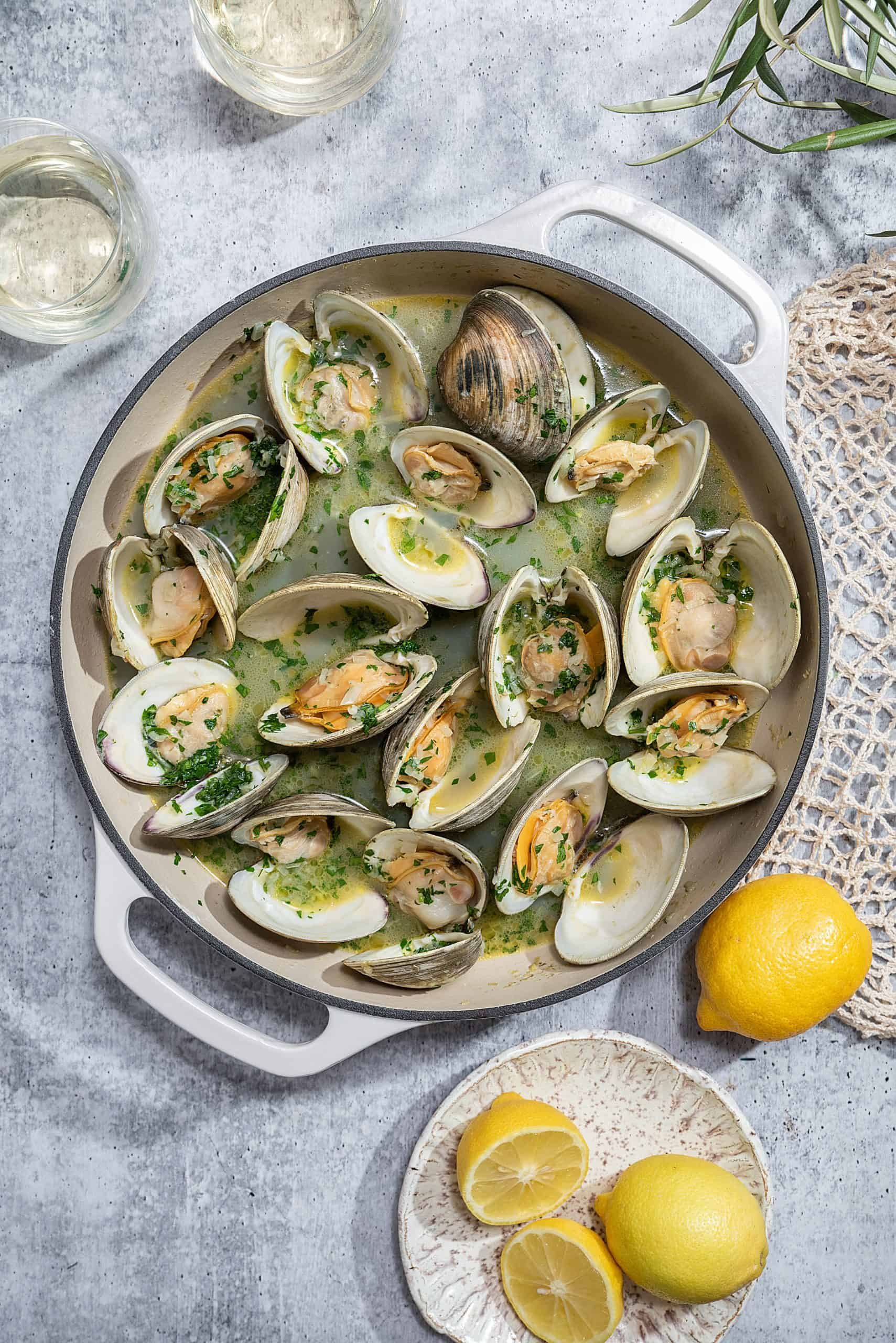 a white pot filled with steamed clams with lemons on the side