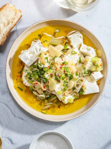 A bowl of marinated feta cheese with olive oil, garlic, shallot and green onion
