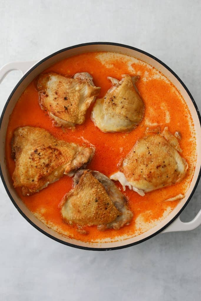 a dutch oven filled with seared chicken thighs in coconut harissa braising liquid
