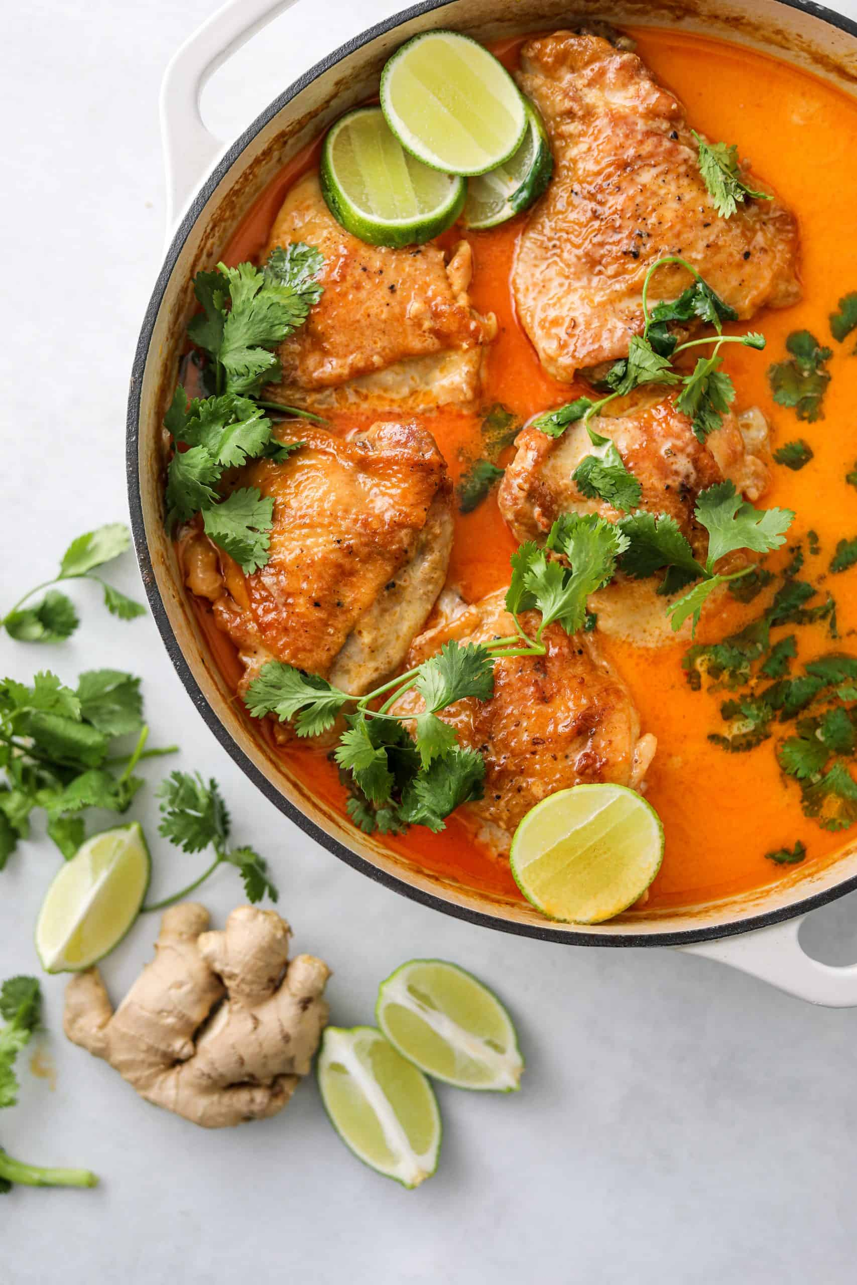 Coconut-Harissa braised chicken in a dutch oven topped with fresh cilantro and lime wedges