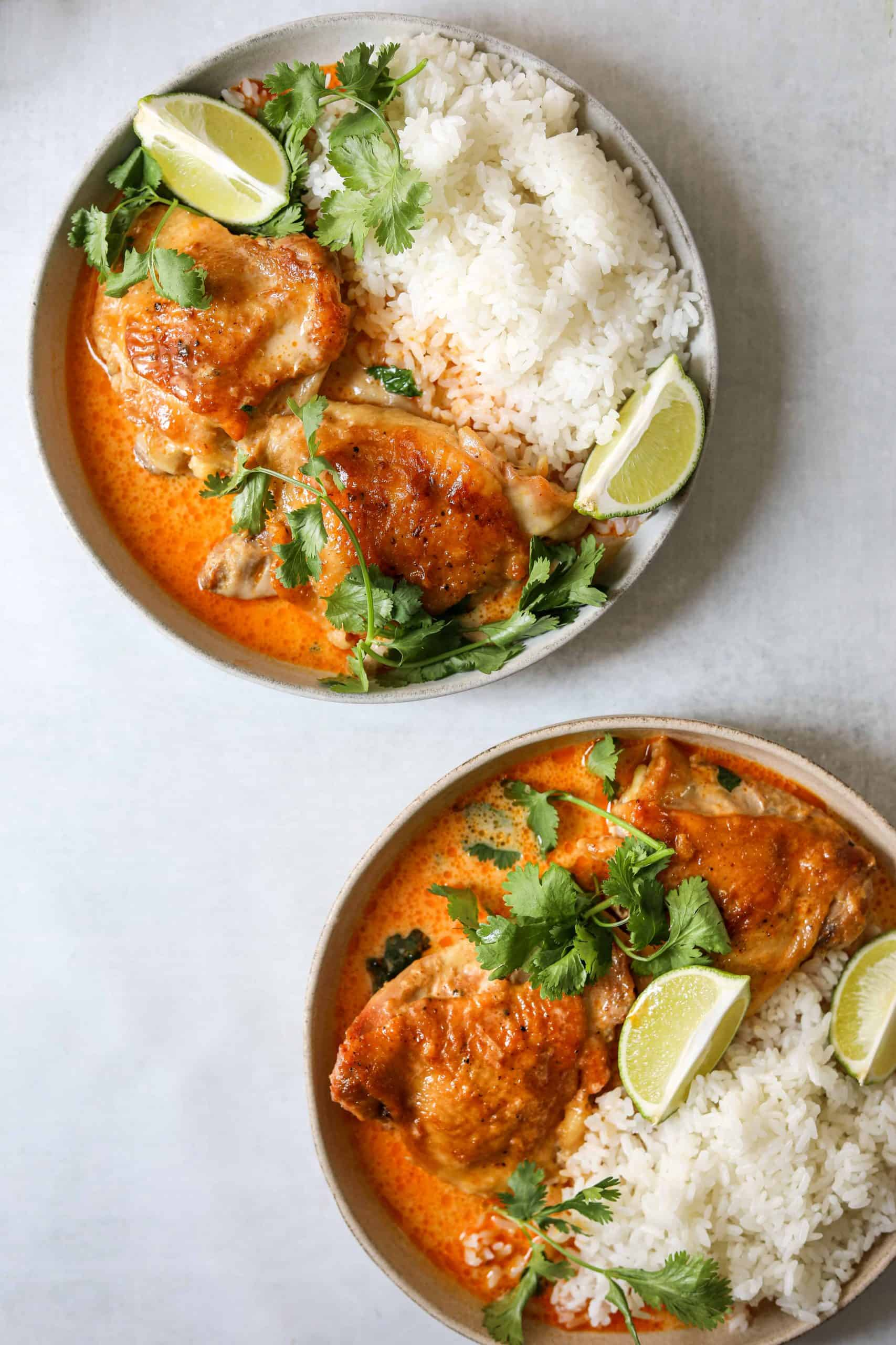 two bowls of coconut-harissa braised chicken with white rice, lime wedges and fresh cilantro