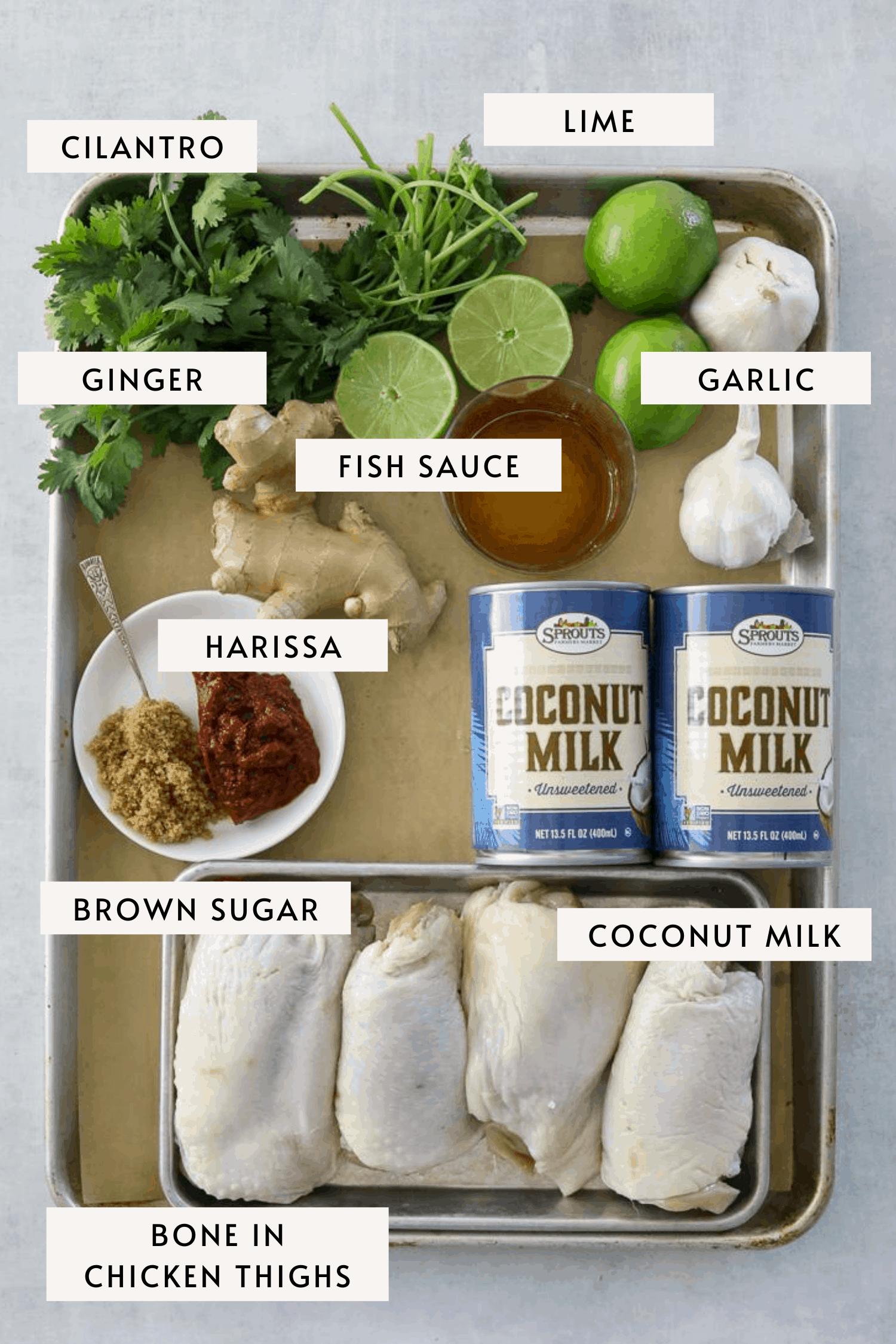 recipe ingredients on a baking tray; chicken thighs, harissa paste, garlic, ginger etc