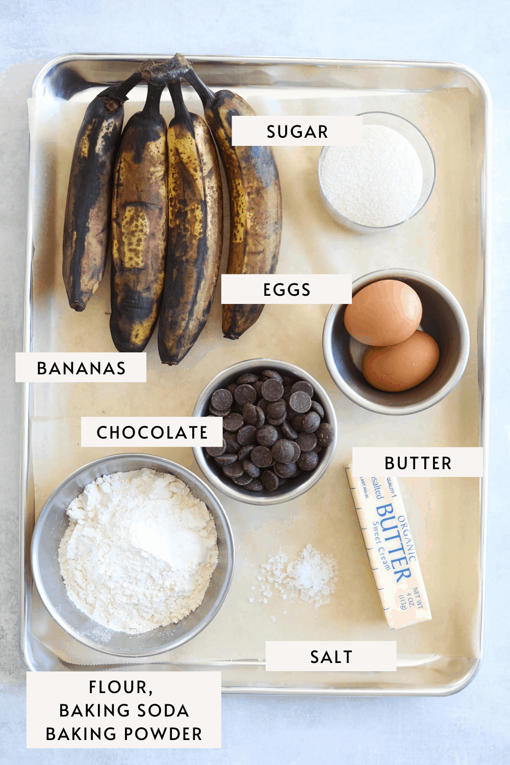 a baking tray with recipe ingredients such as: ripe bananas, chocolate chips, butter and eggs