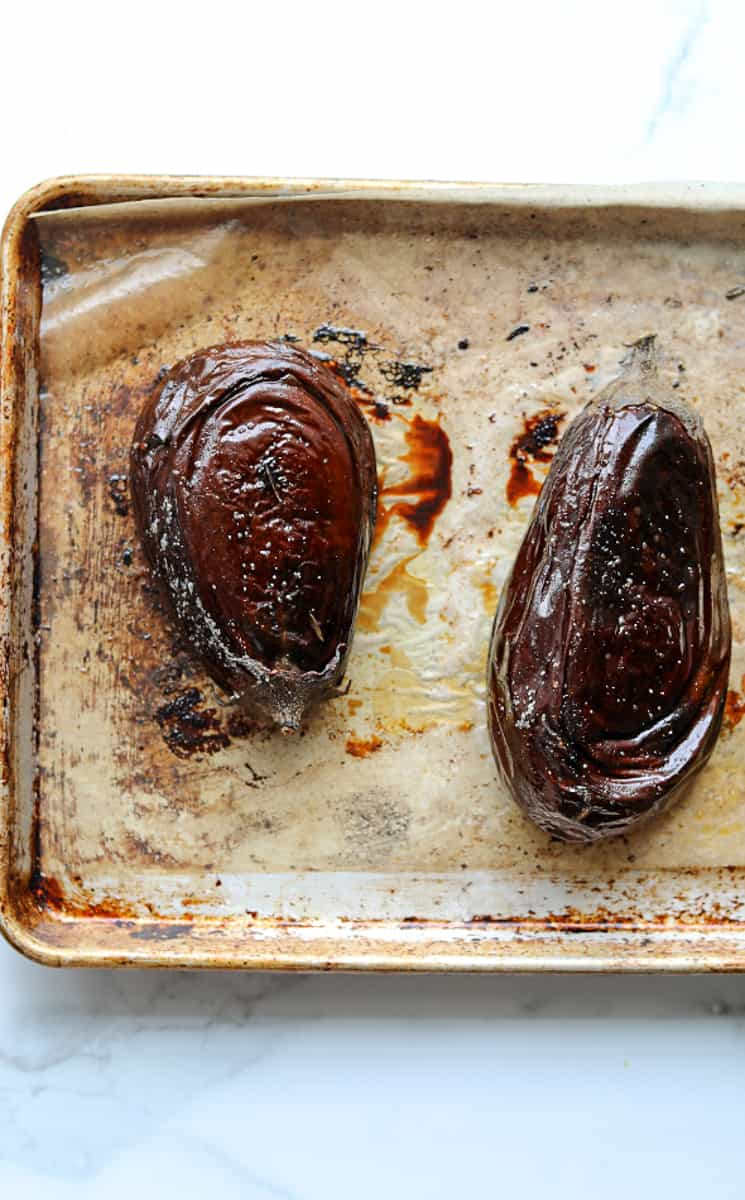 two roasted eggplant on a parchment lined baking tray