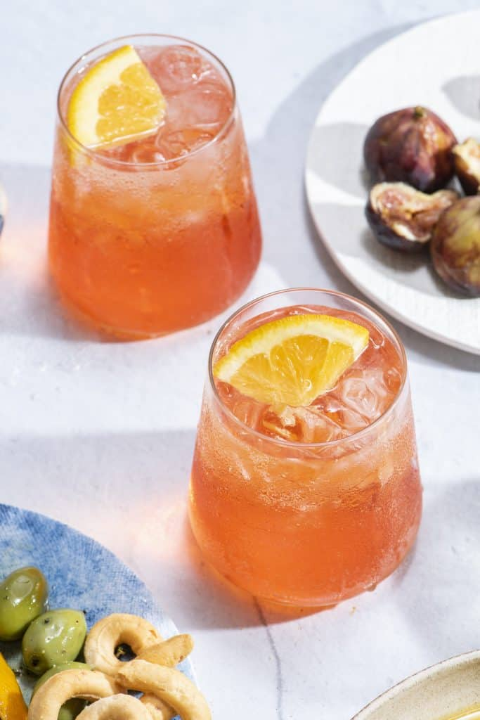 two bright orange aperol spritz cocktails in clear glasses