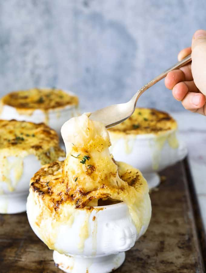 a white crock of vegetarian french onion soup with a spoon dipping into it's melted cheese top