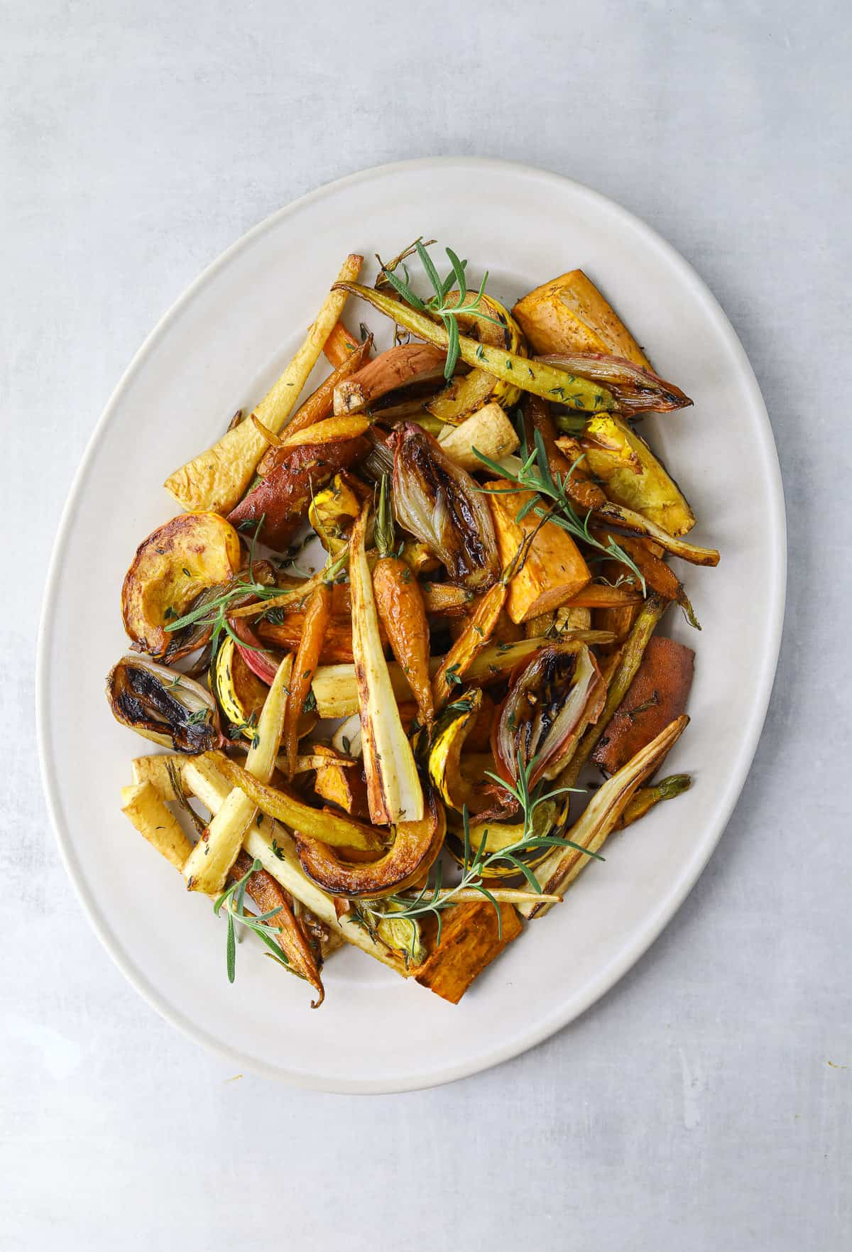 an oval platter filled with roasted root vegetables; carrots, parsnips, shallot, rosemary and thyme