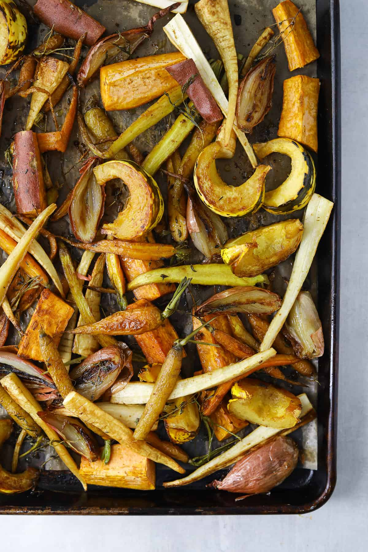 a baking tray golden-brown roasted carrots, squash, sweet potato and shallot