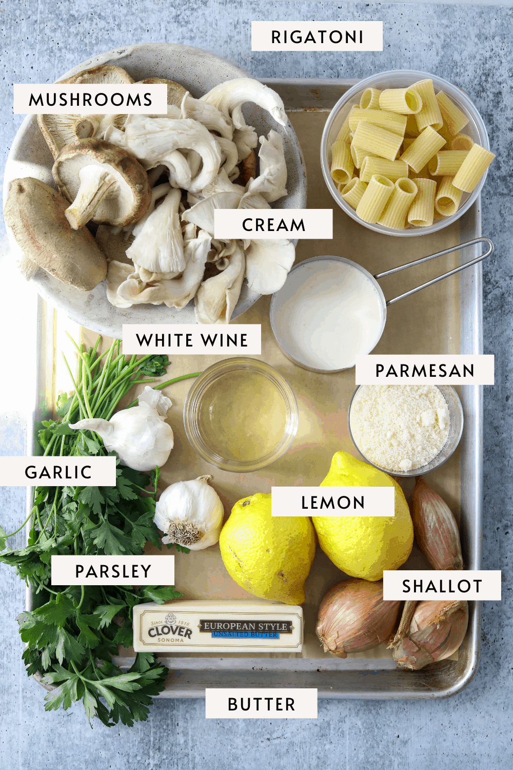 INDIVIDUAL RECIPE INGREDIENTS ON A BAKING TRAY: RIGATONI, MUSHROOMS, CREAM, GARLIC ETC