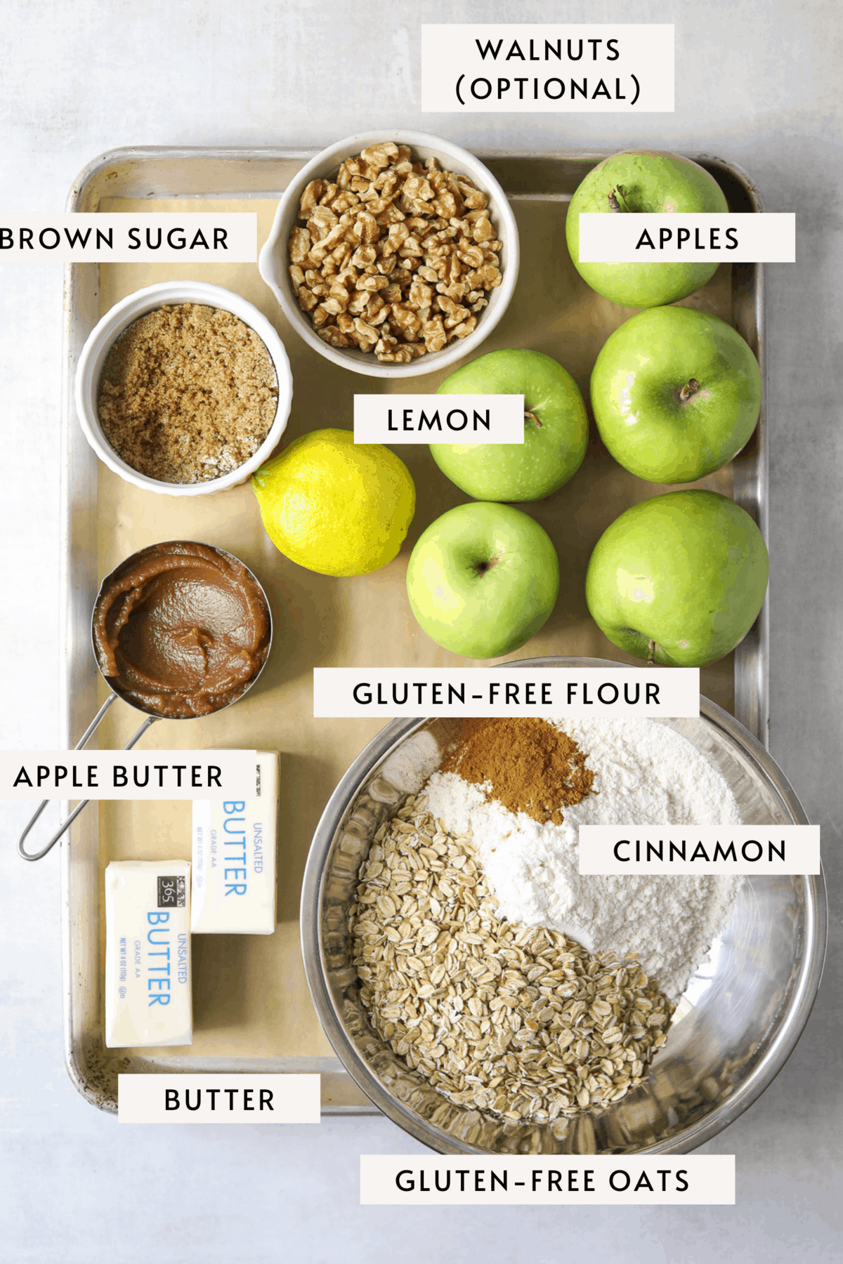 recipe ingredients on a baking tray: apples, walnuts, oats, gluten-free flour, butter etc.
