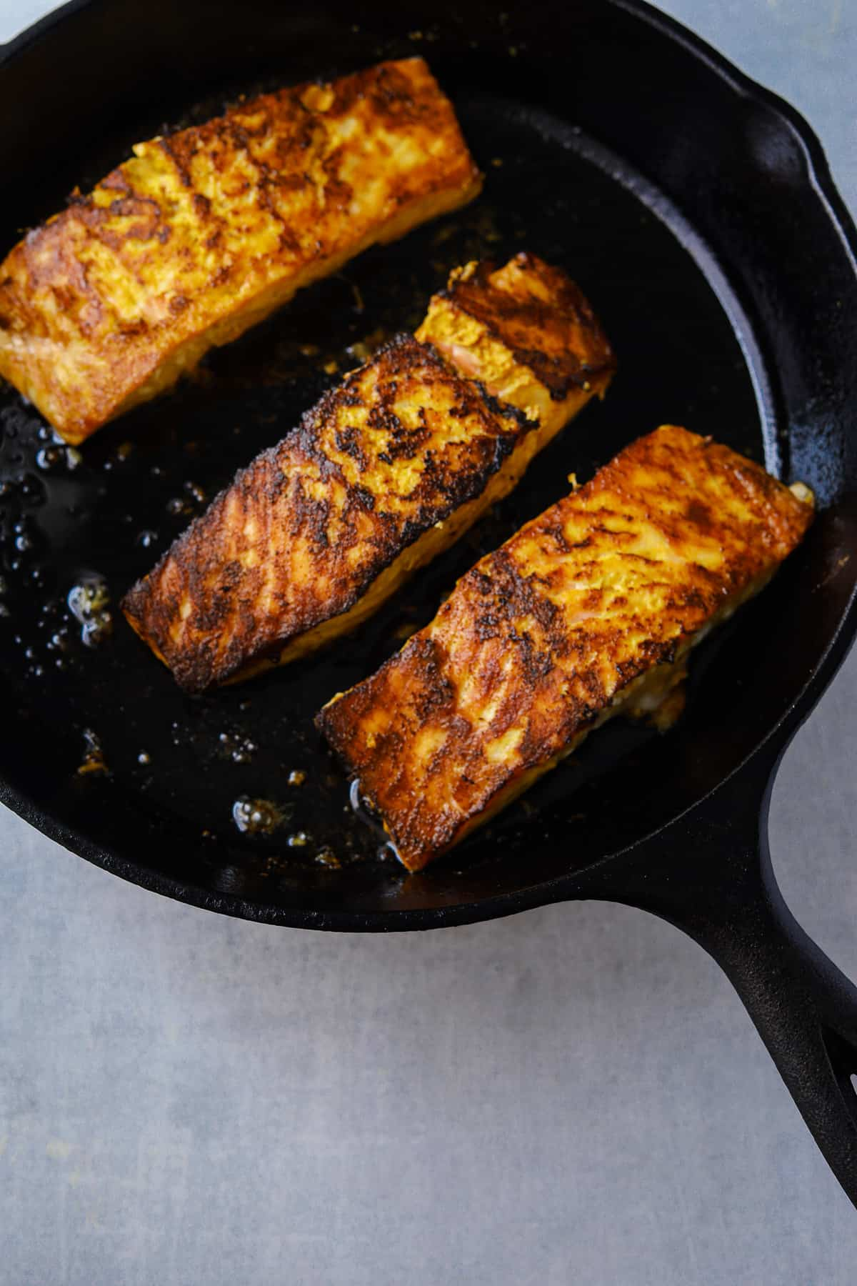 three filets of salmon searing in a cast iron pan