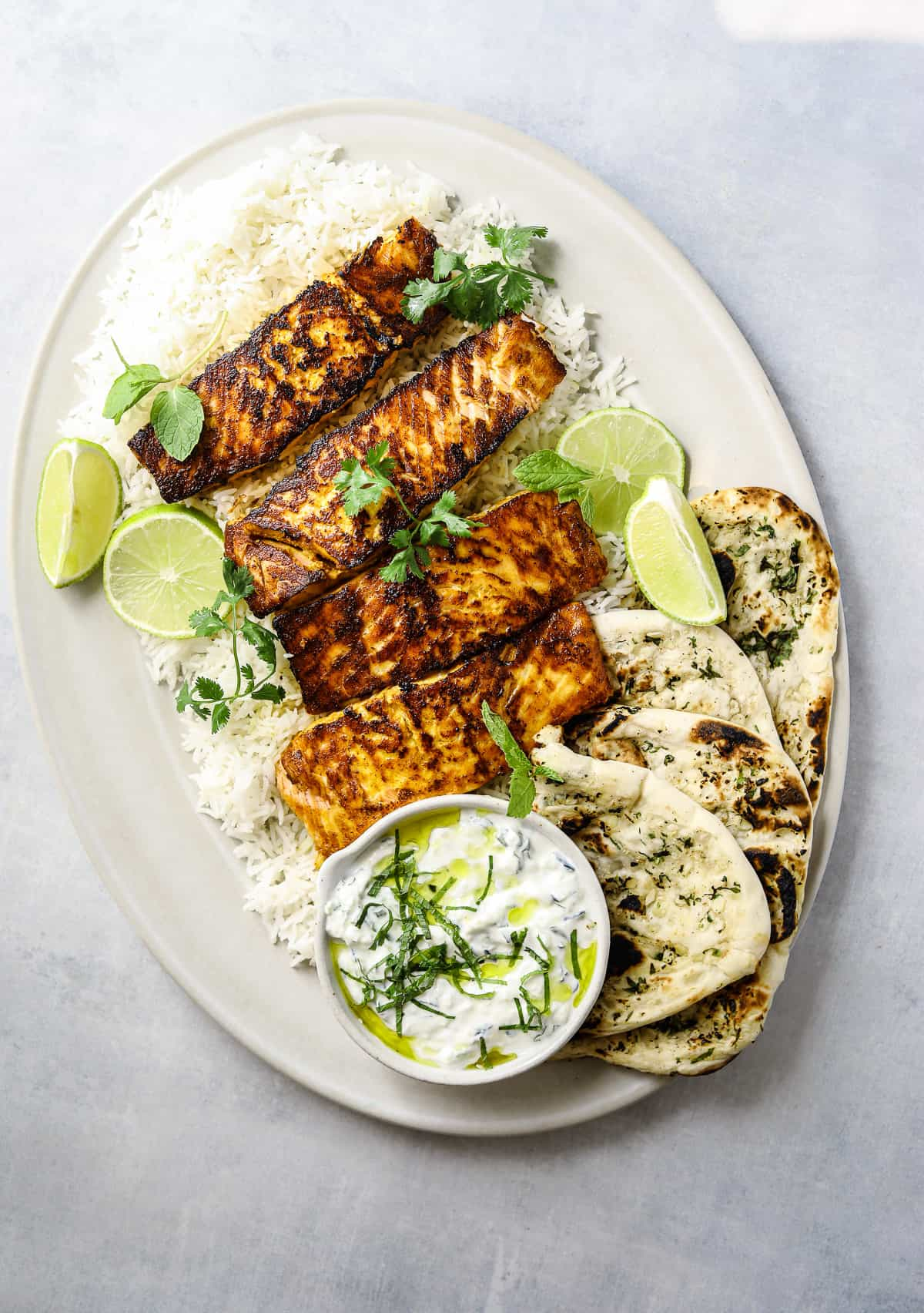 a large oval platter of tandoori salmon filets on top of rice with naan bread and raita sauce