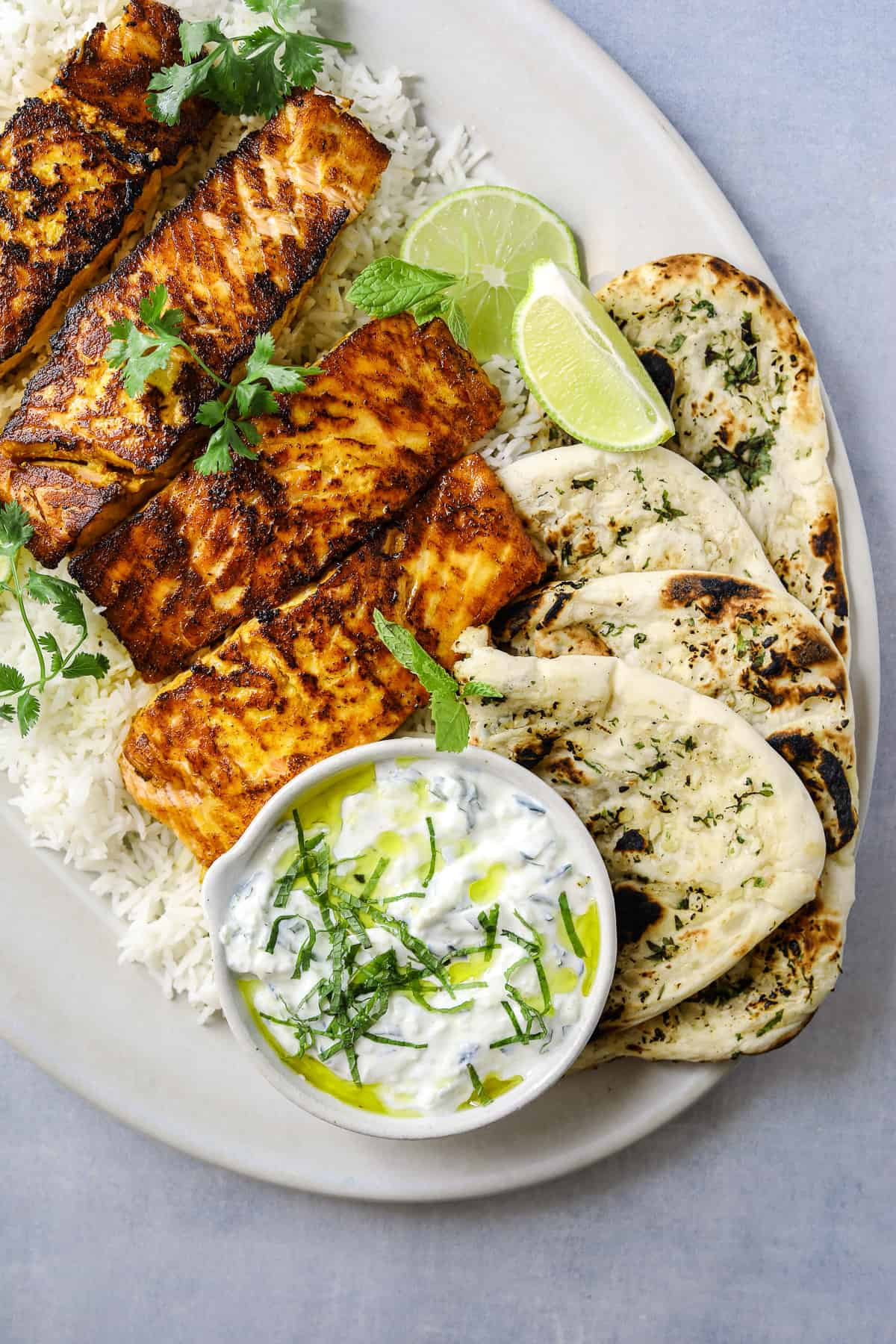 a platter with three filets of salmon on top of rice surrounded but naan bread and cucumber raita