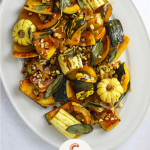 a white oval platter filled with roasted squash, sage leaves, hazelnuts and, raisins.