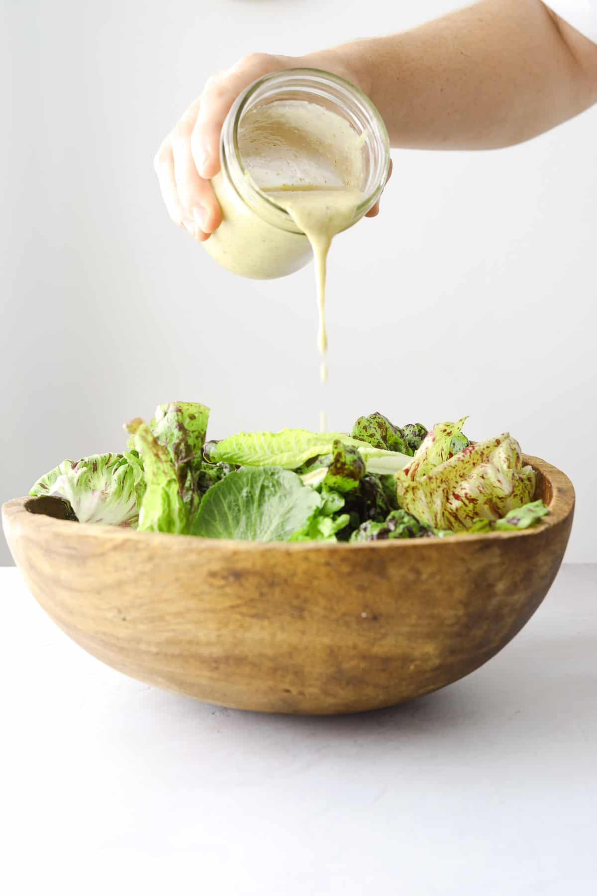 a jar of vinaigrette being poured into a wooden salad bowl filled with lettuce