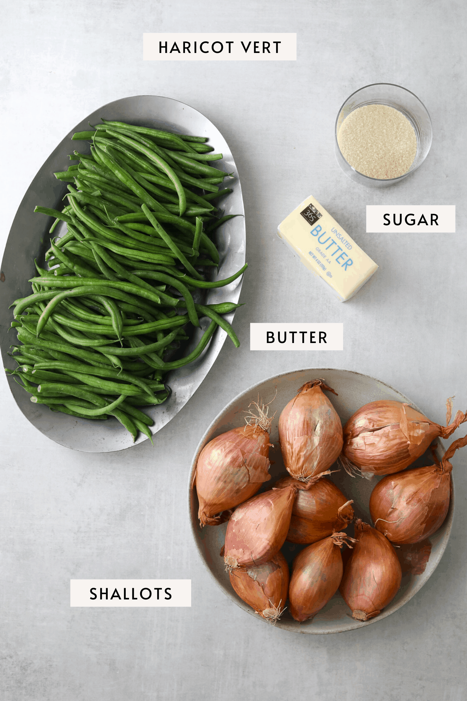 a bowl of shallots, french green beans on a sliver tray a stick of butter and small bowl of sugar