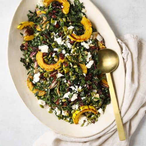 a large oval platter filled with roasted delicata squash salad, a gold spoon and linen napkin