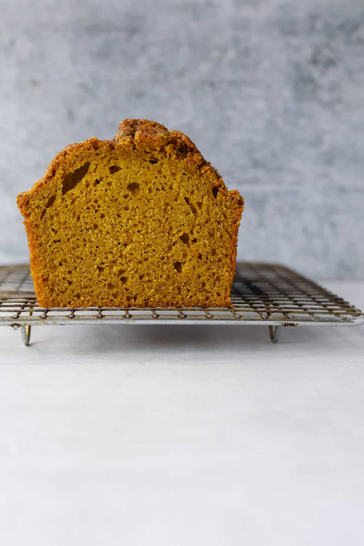 a slice of gluten-free pumpkin loaf on a cooling rack with a blue background