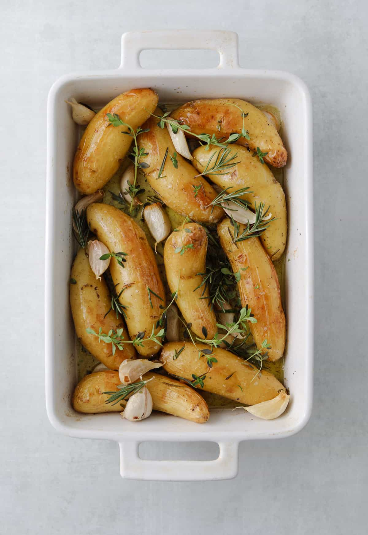 roasted potatoes in a white rectangle baking dish with herbs, garlic and oil on a blue background