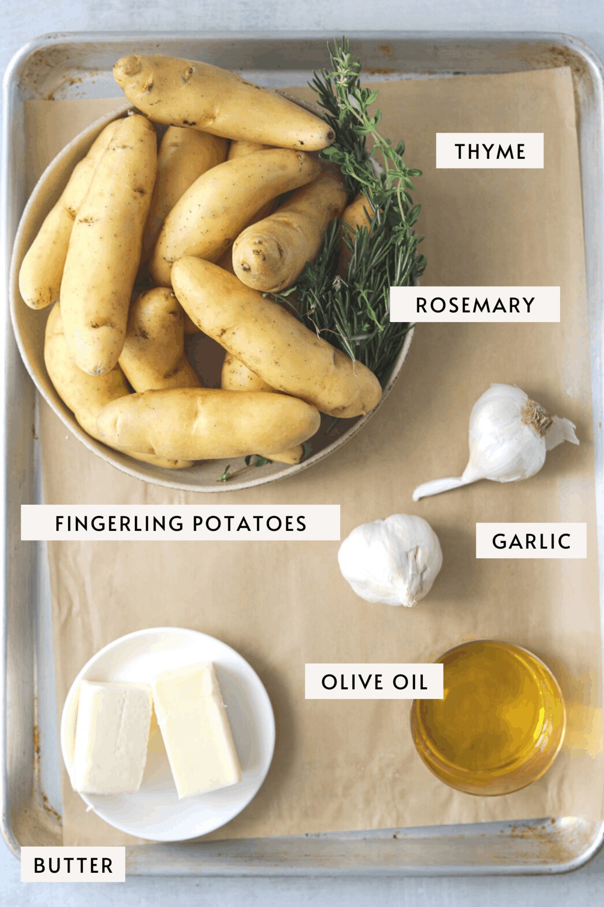 recipe ingredients on a baking tray: a bowl of fingerling potatoes, garlic, herbs, butter on a white plate and oil in a glass dish
