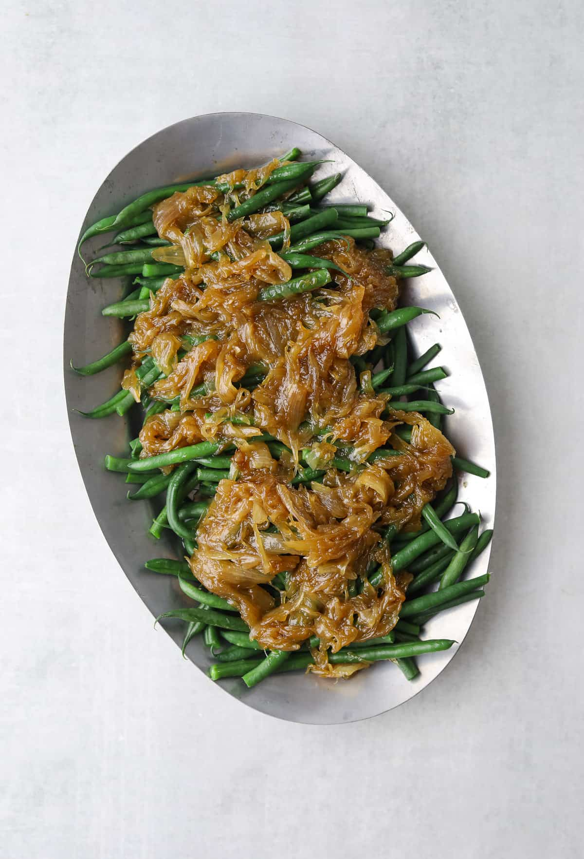 a silver platter filled with french green beans topped with golden brown caramelized on a blue background