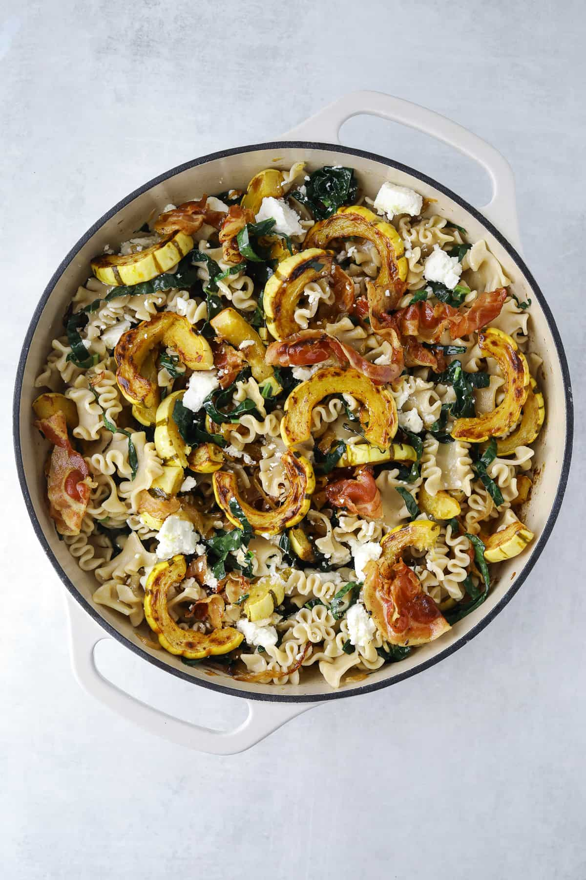 a cream colored pot filled with pasta, goat cheese, pancetta, kale and roasted delicata squash