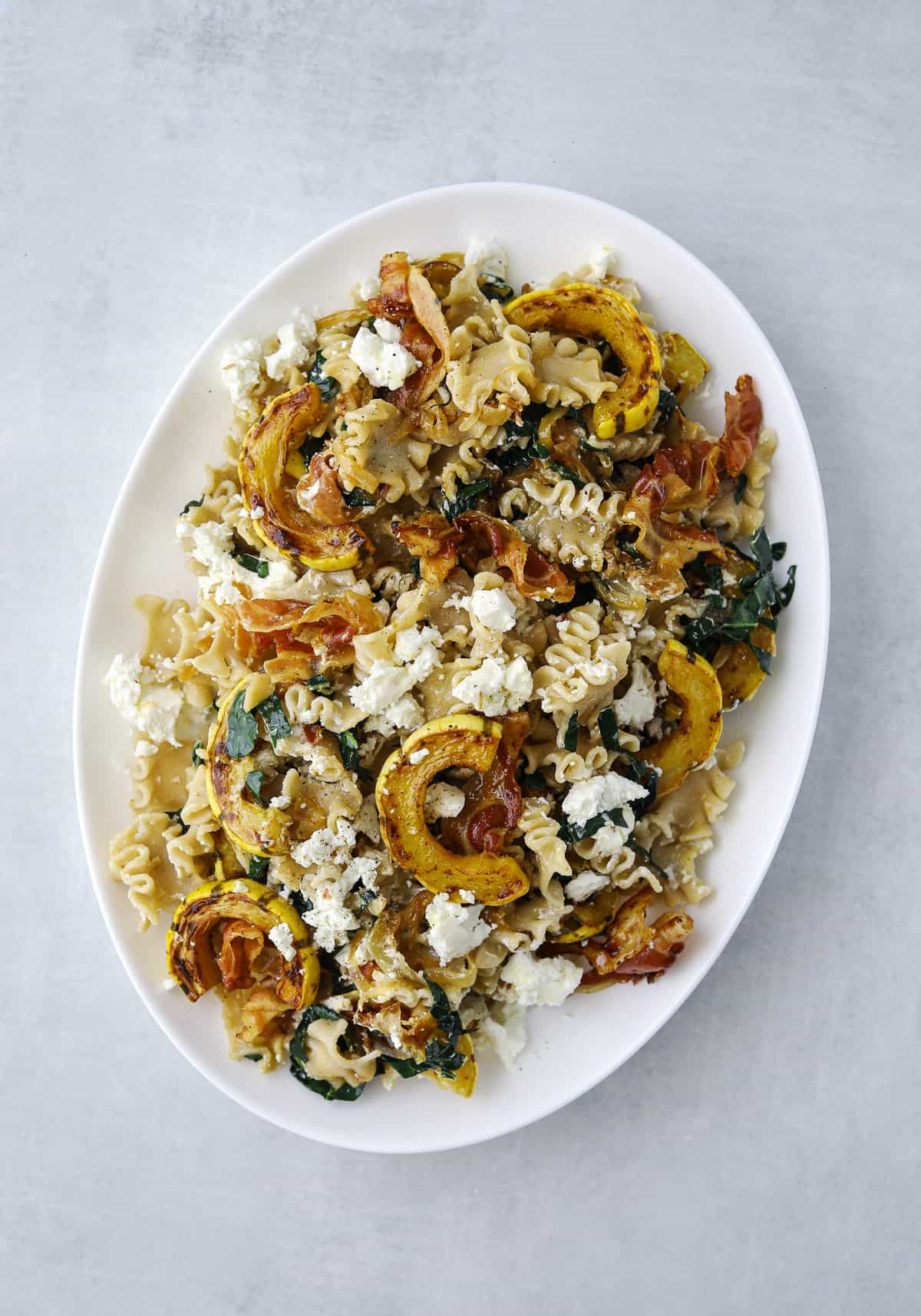 a white oval platter filled with pasta, goat cheese, roasted squash, and crispy pancetta