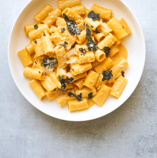 a white bowl filled with creamy pumpkin rigatoni and topped with crispy fried sage