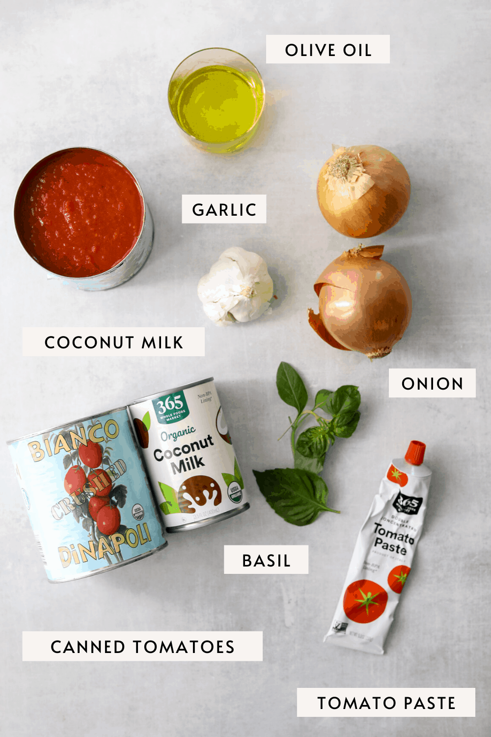 recipe ingredients on a blue background; canned tomatoes, olive oil, onion, garlic, basil, coconut milk
