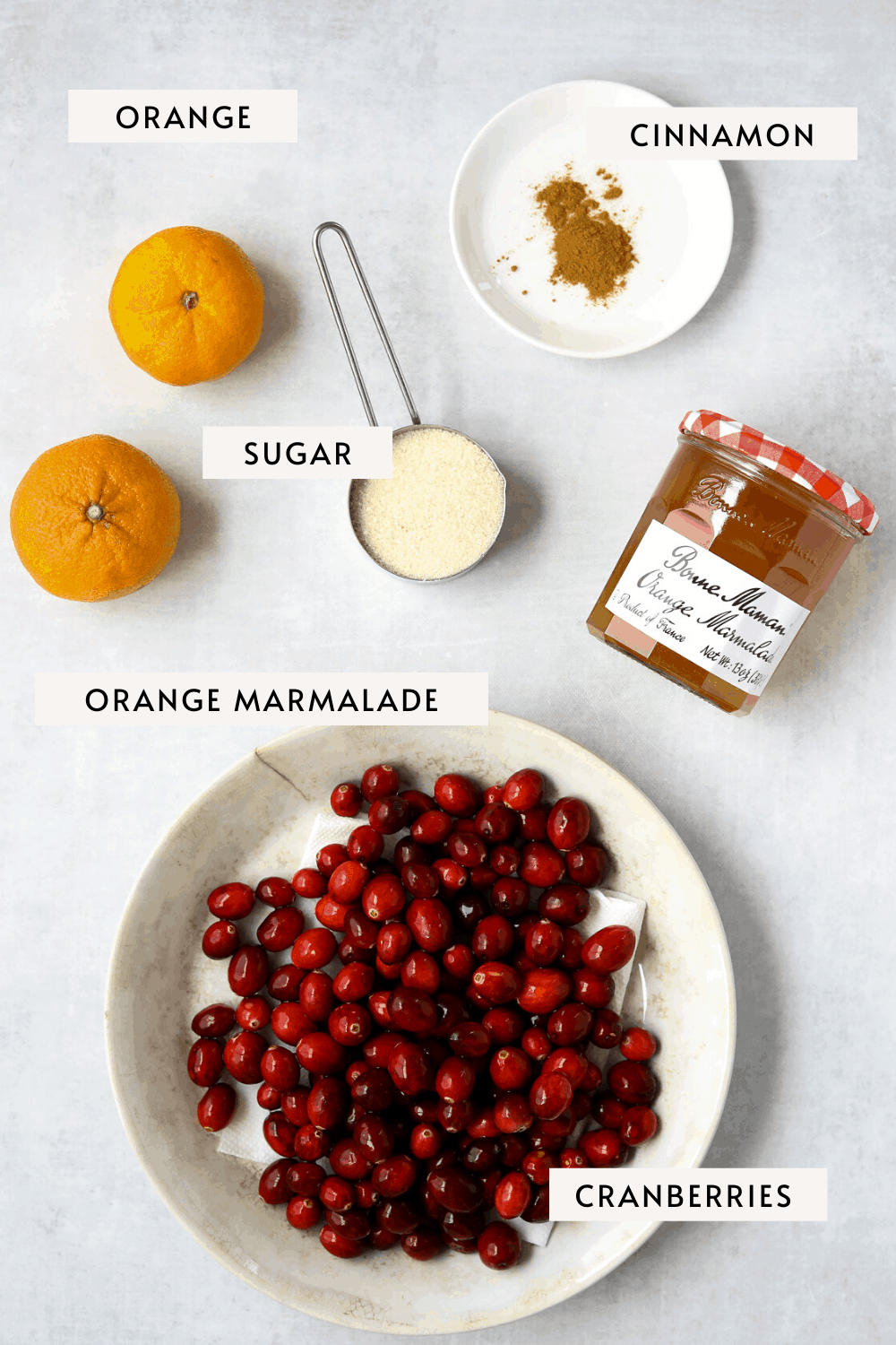 a bowl of fresh cranberries, two small oranges, a pinch of cinnamon, a jar of orange marmalade