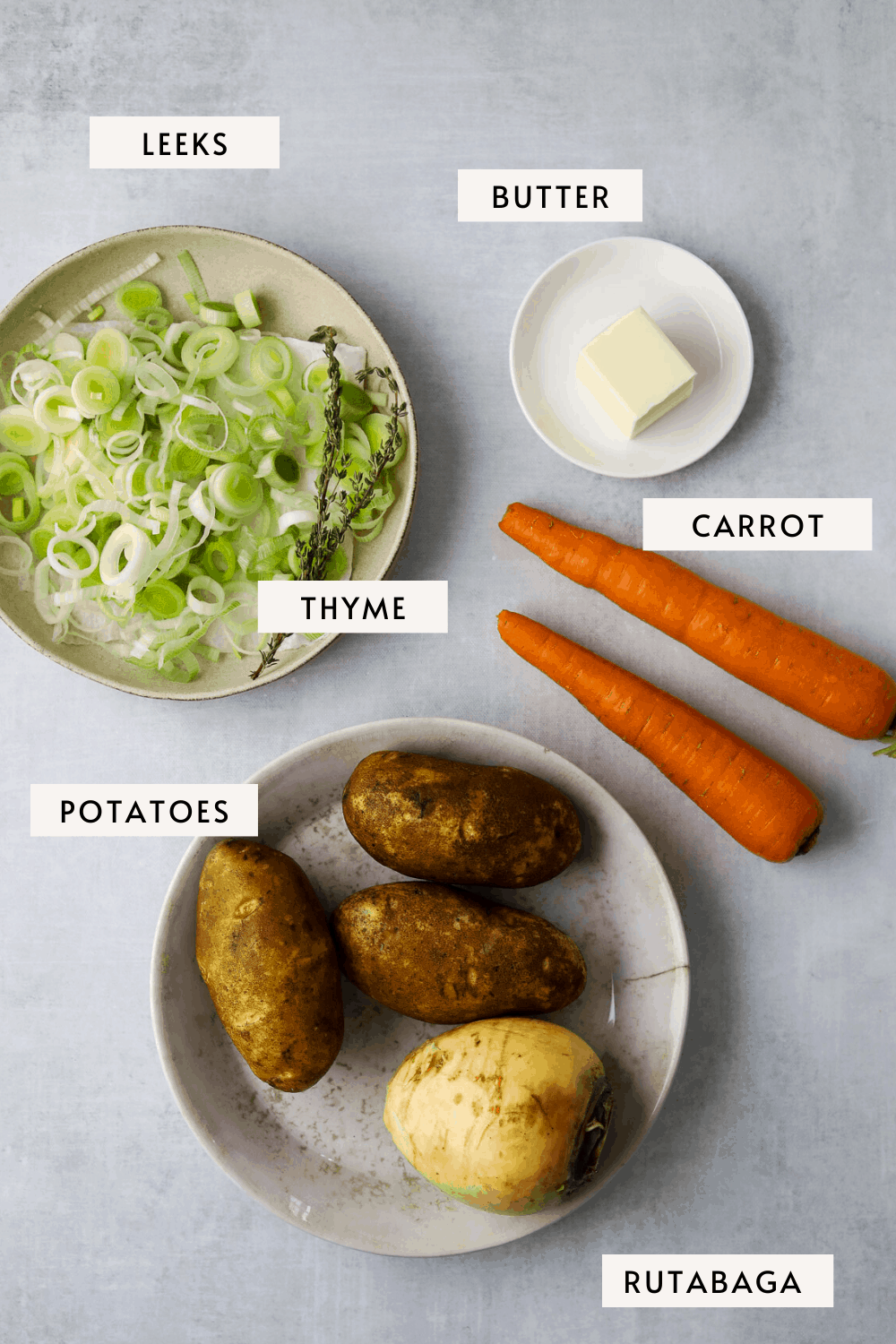 recipe ingredients, two carrots, chopped leeks in a bowl, fresh thyme, potatoes, rutabaga