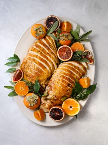 two roasted turkey breasts thinly sliced on an oval serving platter surrounded but citrus, herbs and persimmons