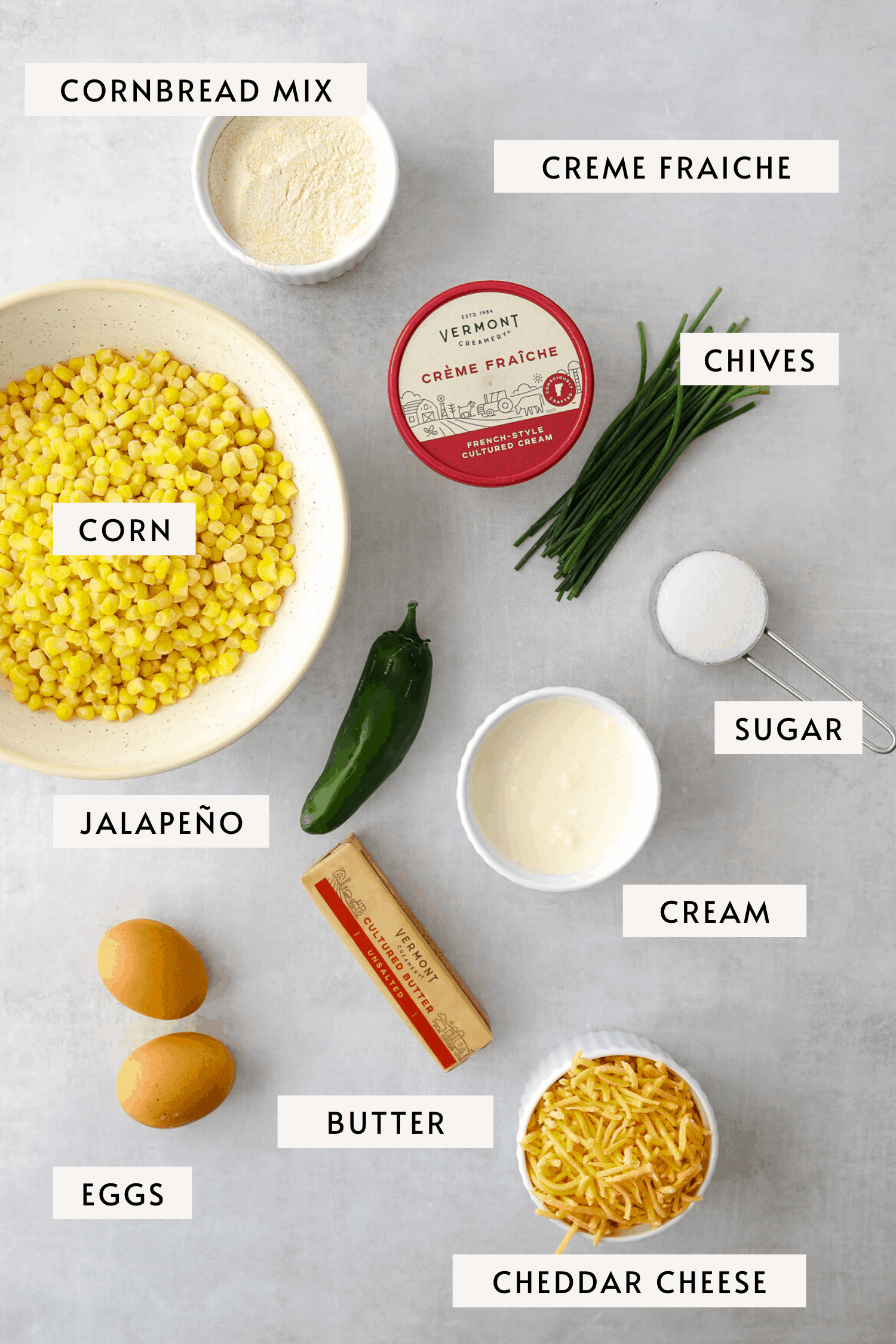 recipe ingredients on a blue background, eggs, cheddar cheese, corn kernels, jalapeño, sugar, chives, butter, cream