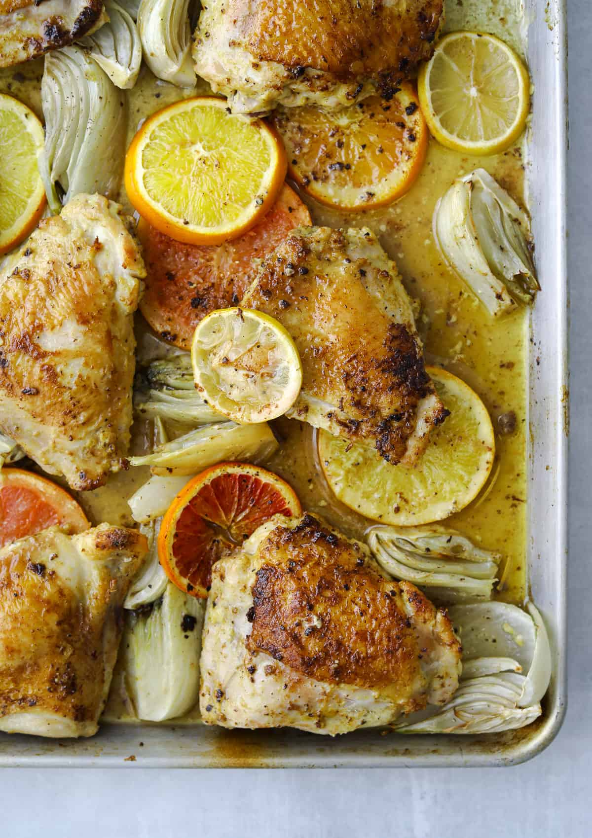 golden brown roasted chicken thighs with citrus, fennel, olive oil on a baking tray