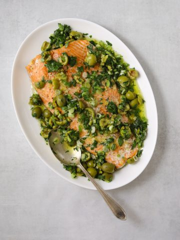 a large white platter of salmon topped with a fresh green sauce of crushed olives, parsley and green onion