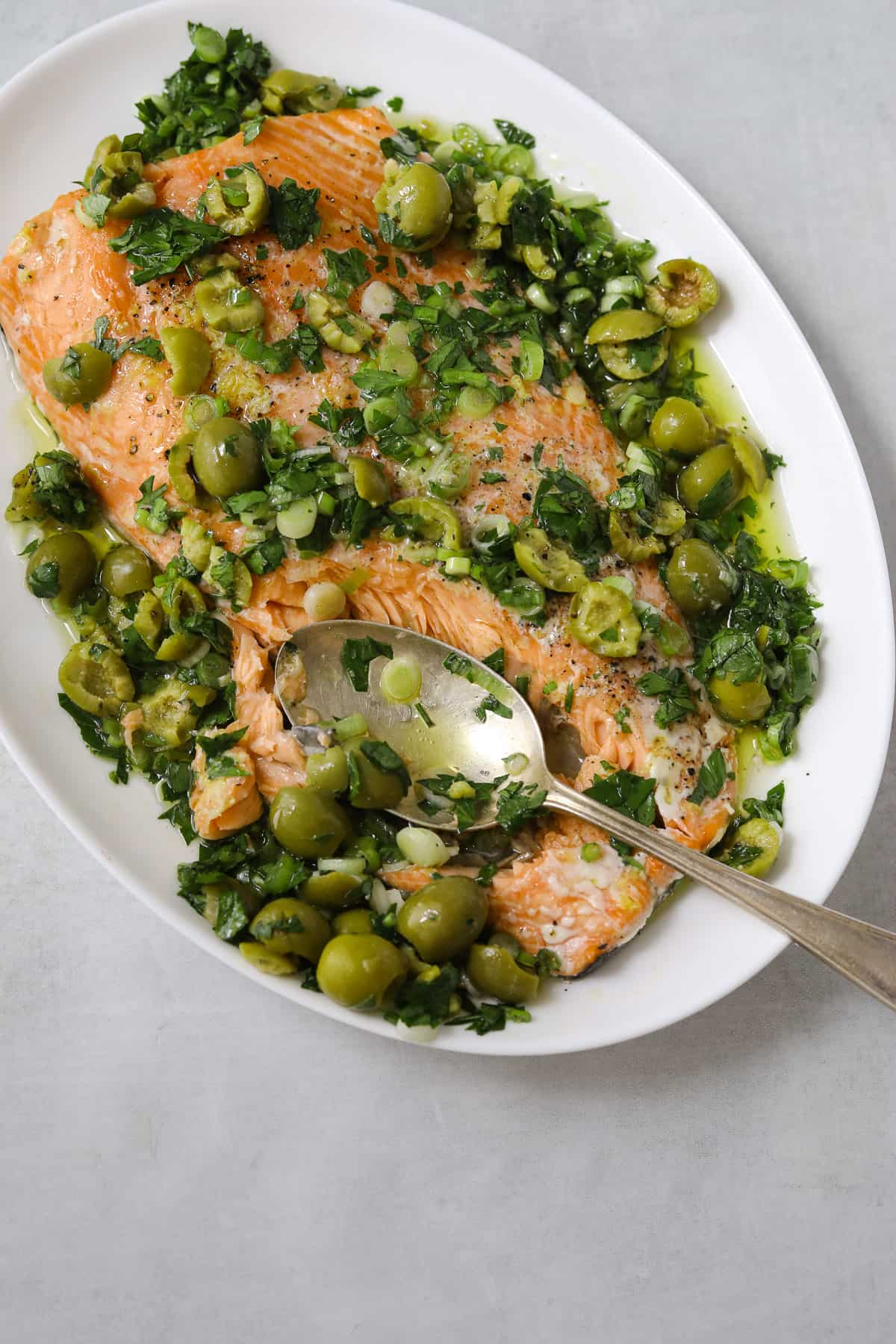a white platter with slow-roasted salmon topped with green olive salsa verde and a silver spoon breaking into the salmon