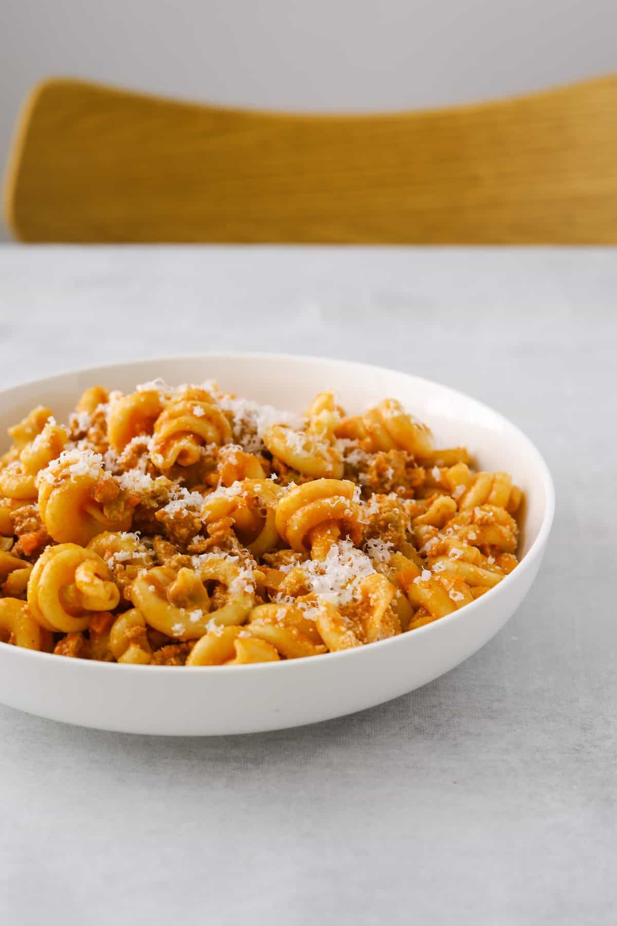a white bowl filled with turkey bolognese pasta, topped with grated parmesan cheese, background is blue