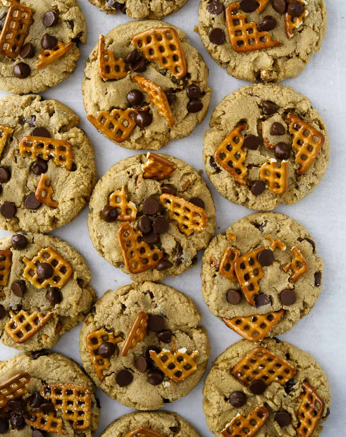 ten peanut butter chocolate chip pretzel cookies on a grey background