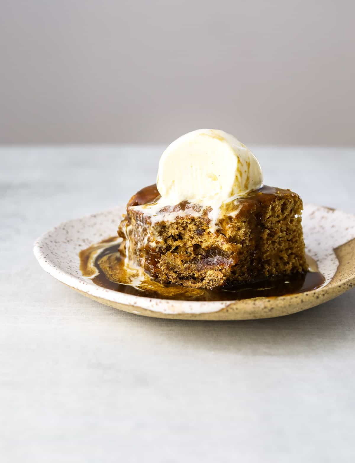 a square of date cake, topped with ice cream and caramel sauce with a bite missing