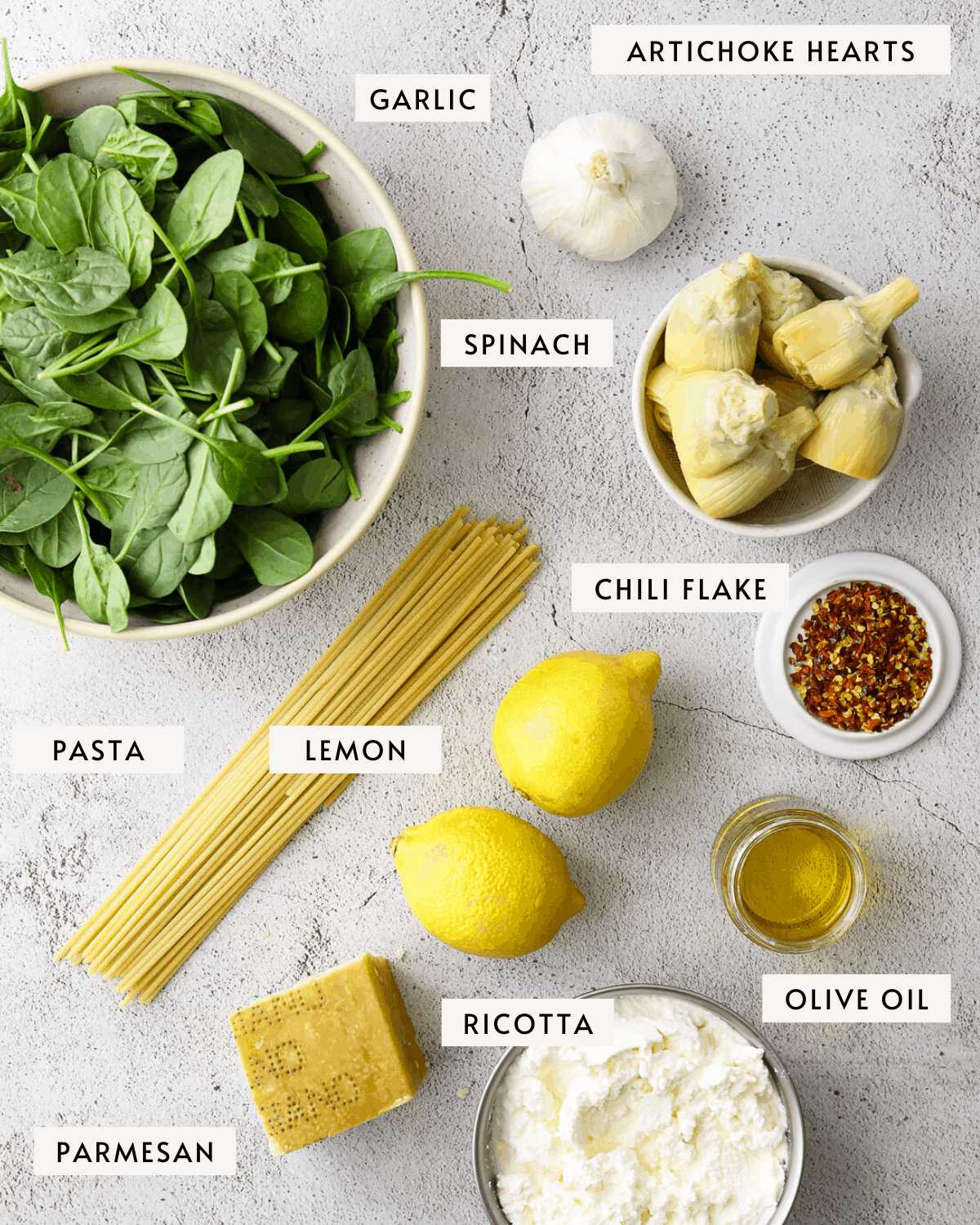 recipe ingredients individually portioned out; artichoke hearts, spinach, lemon, ricotta cheese, dried pasta etc.
