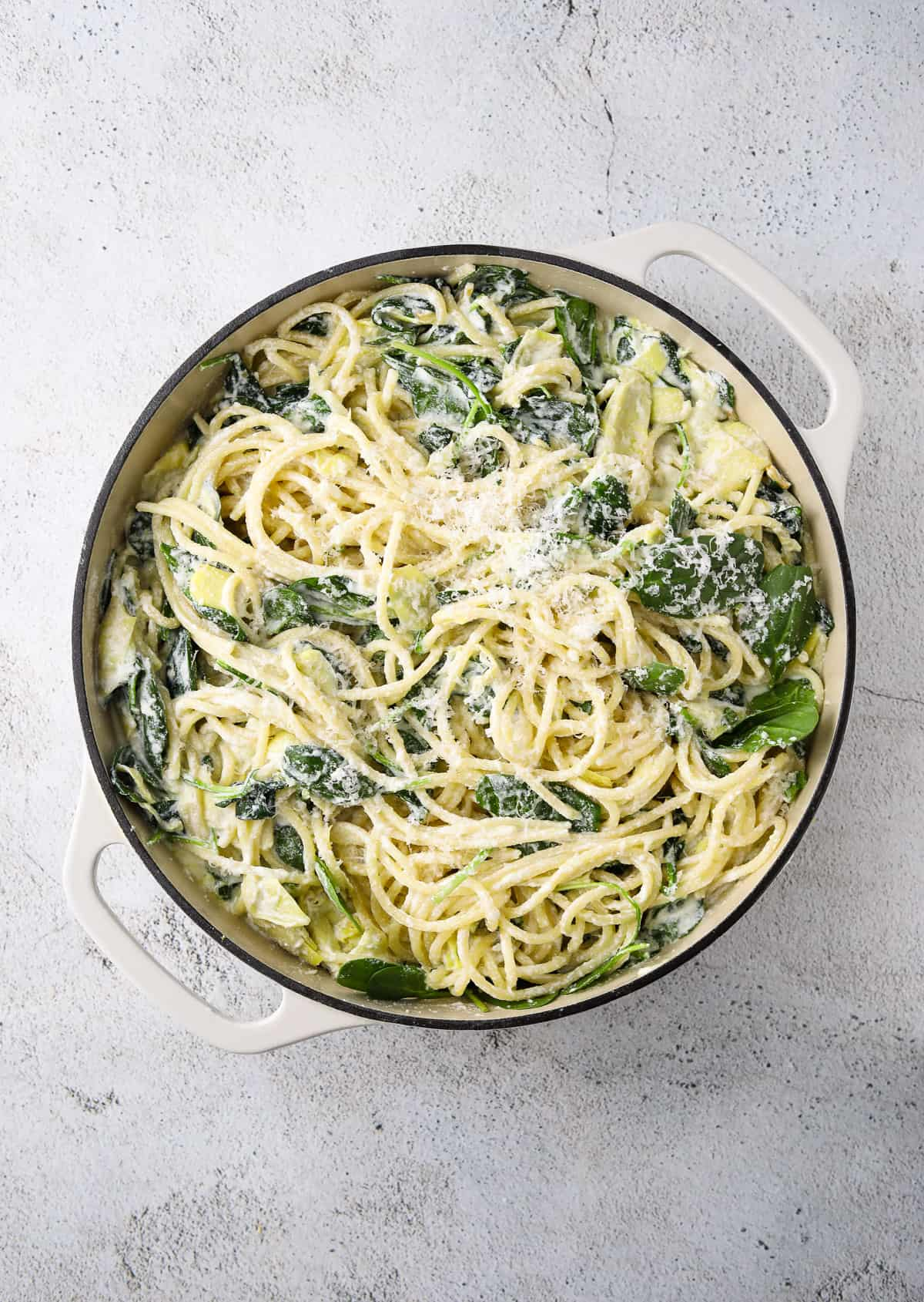 a large pot filled with lemon ricotta pasta topped with grated parmesan cheese and lemon zest