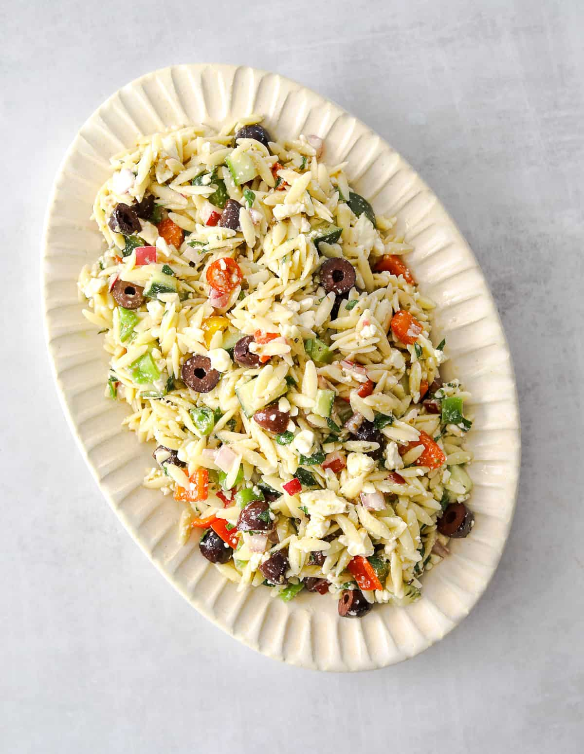 an oval platter filled with colorful orzo greek salad