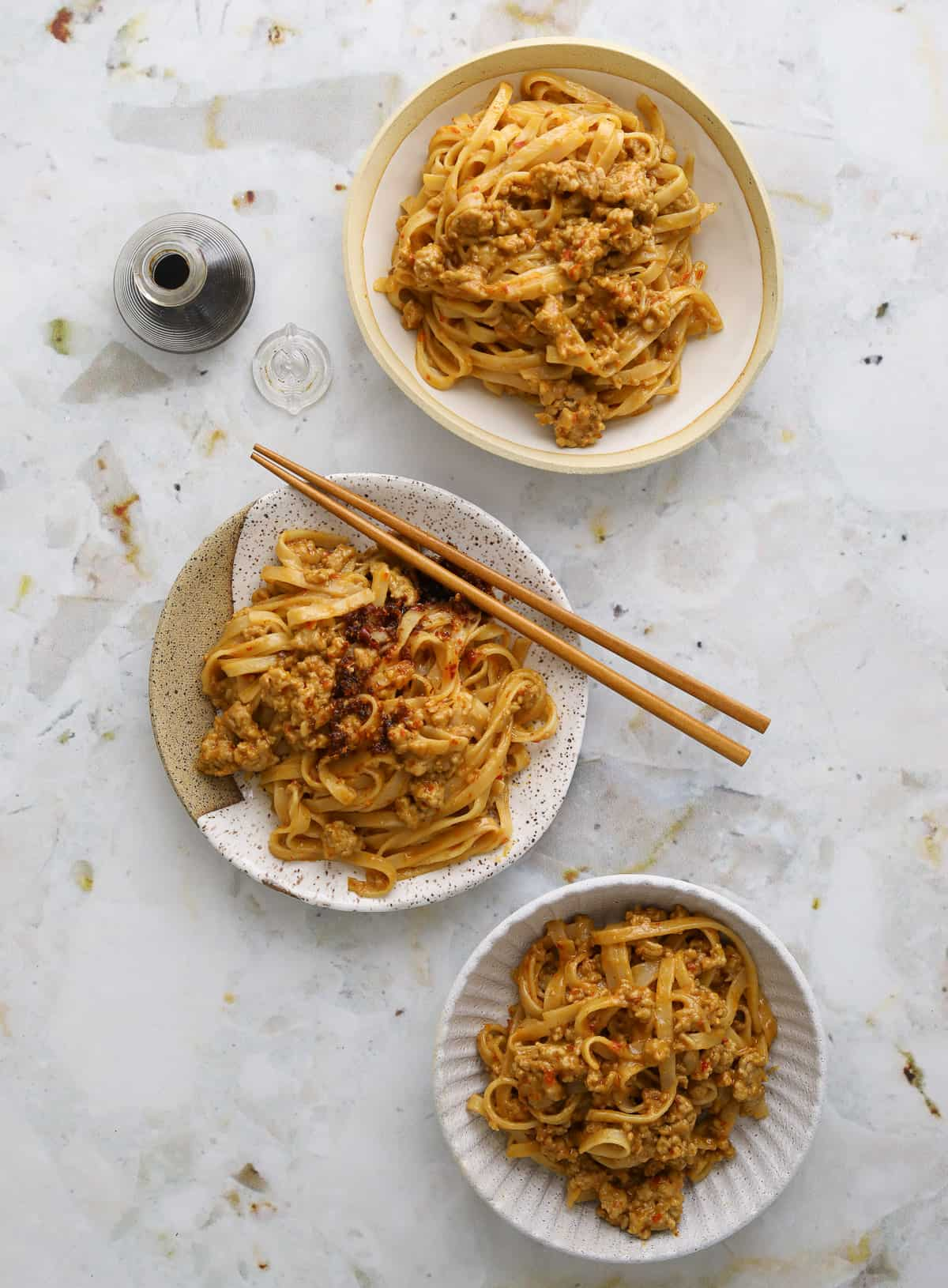 three bowls of spicy pork and peanut noodles with chop sticks and a small bottle of soy sauce